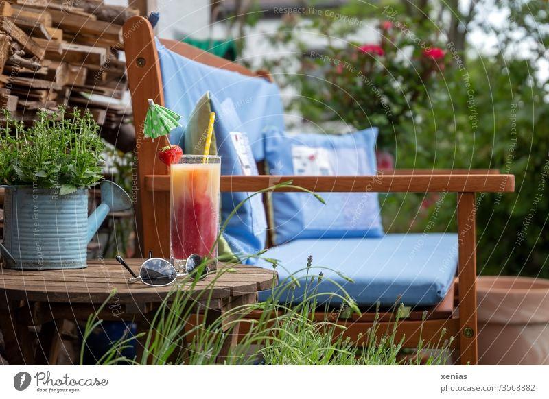 Kiba mit Trinkhalm, Erdbeere und Schirmchen, Sonnenbrille, sowie Gartenbank mit blauen Kissen stehen bereit für eine kleine Auszeit sitzplatz Getränk Erholung