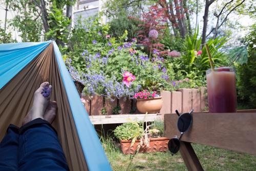 Füße in einer Hängematte mit Blick auf den Garten und bereitgestellten Drink - Tiefenentspannung garantiert Entspannung Erholung Sonnenbrille Getränk Saft Glas