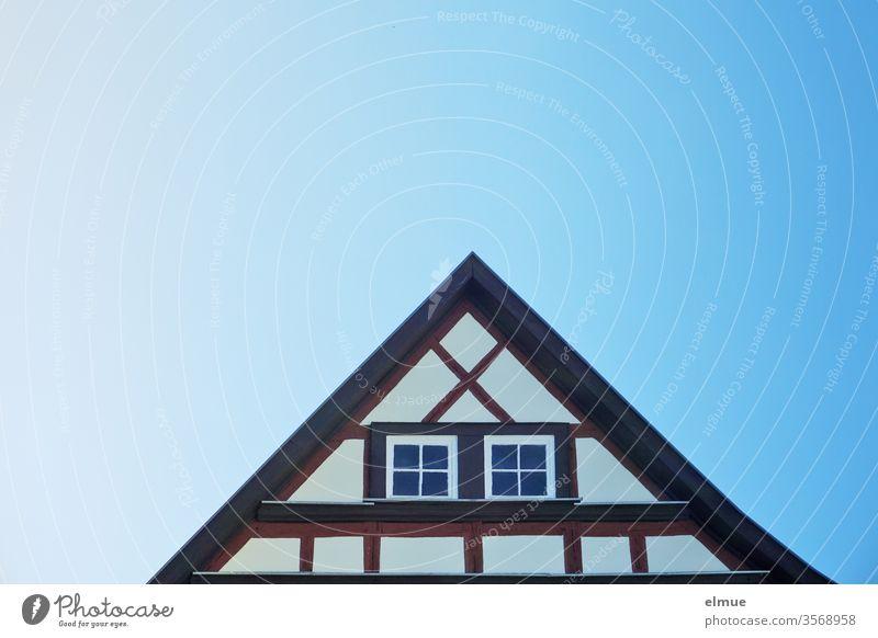 Giebel eines renovierten Fachwerkhauses mit zwei Fenstern und blauer Farbverlauf im Himmel Dreieck wohnen modern Architektur Fassade Gebäude Bauwerk Dach