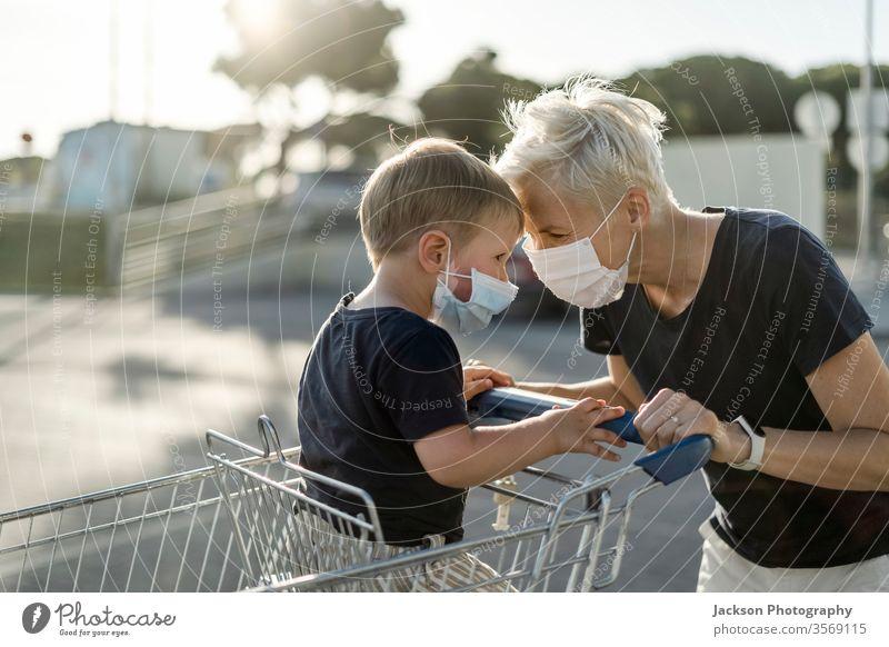 Mutter spielt fröhlich mit dem Kind, das im Einkaufswagen sitzt. Beide tragen eine schützende Gesichtsmaske. Frau Mundschutz spielen Karre Werkstatt Baby