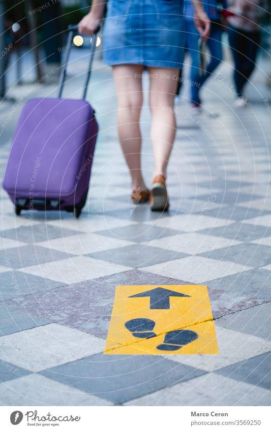 Tourist mit Koffer, der auf einer städtischen Straße geht, die mit Sicherheitsschildern für den sozialen Abstand gekennzeichnet ist Reisender covid-19