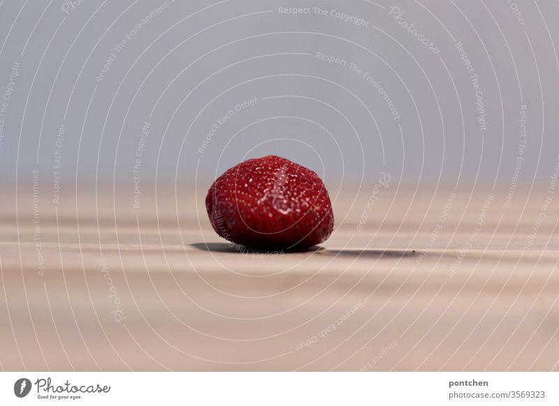 Eine einzelne Erdbeere liegt auf einem Holztisch und wirft einen Schatten schatten gesunde ernährung obst vitamine rot Lebensmittel Frucht Bioprodukte lecker