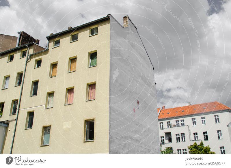 Ruhe vor dem Sturm im Kiez Neukölln Stadthaus Fassade Architektur Brandmauer Wolken Fenster Mietshaus Hinterhof authentisch Ecke Wolkenformation Wohngebiet