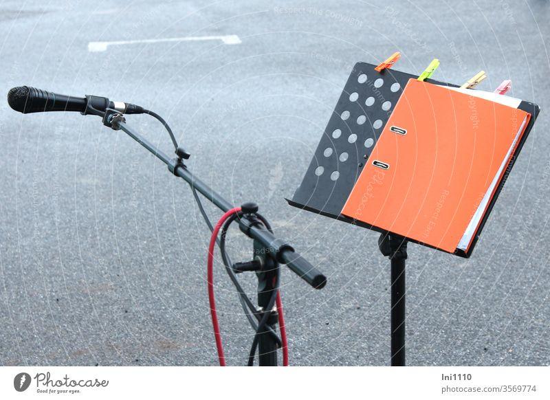 Pause - das Mikrofon ist verlassen - das Manuskript ist zugeschlagen Notenständer Ständer Metall Ordner orange durchlöchert geschlossen Wäscheklammern Halter