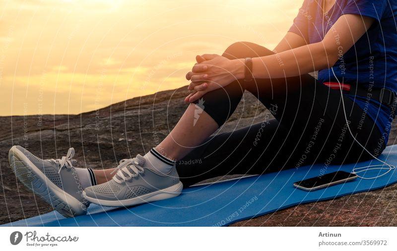 Frau sitzt und entspannt auf Yogamatte und hört Musik über Smartphone am Steinstrand am Meer. Frau trainiert im Freien. Fites Mädchen trägt Smartband. Gesunder, entspannter Lebensstil. Entspannen in den Sommerferien.