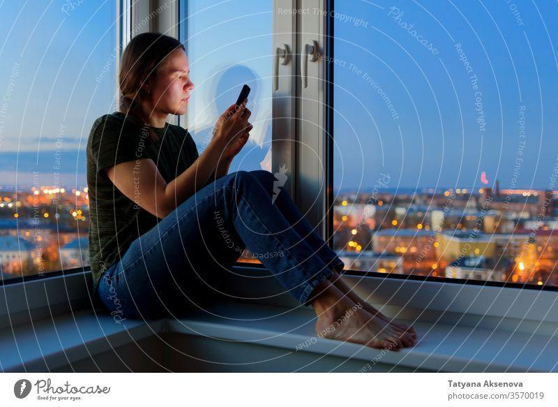Junge Frau, die nachts auf der Fensterbank sitzt und telefoniert benutzend Telefon online Nacht Fenstersims Schlafstörung Sucht Internet Bildschirm schlafen