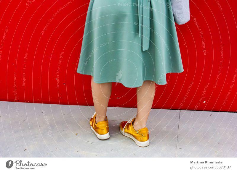 Dame mit goldenen Turnschuhen und grünem Rock vor roter Wand Erwachsener attraktiv Tasche blau leger Kleidung Mode Schuhe Glück glücklich Lebensstil Bürgersteig