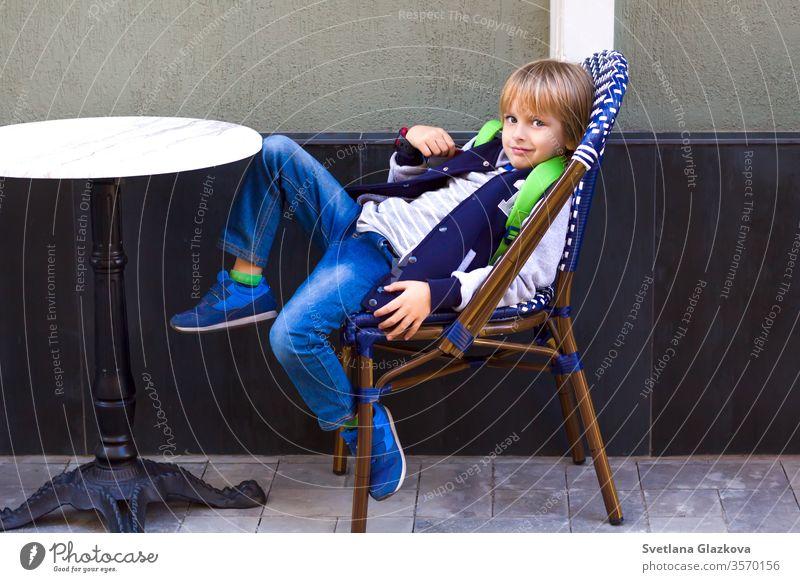 Der Junge sitzt auf einem Stuhl in einem Stadtcafé. jung im Cafe Café im Cafe sitzend Personen-Couchtisch Hipsters-Restaurant Familienrestaurant Kind Großstadt