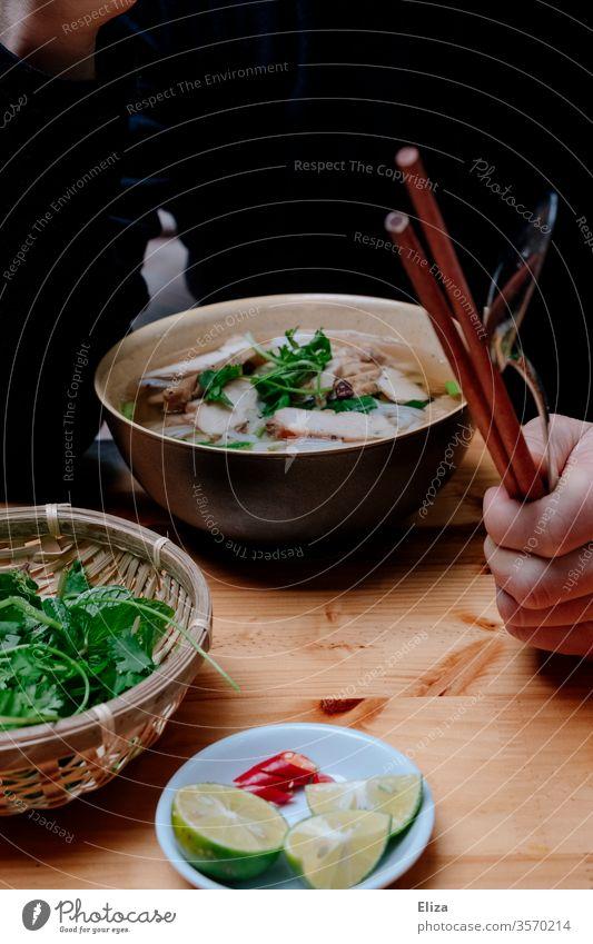 Eine Person sitzt mit Essstäbchen in der Hand vor einer leckeren Pho Suppe in Vietnam Essen Stäbchen Limette frisch heiß Kräuter traditionell Mahlzeit Schüssel