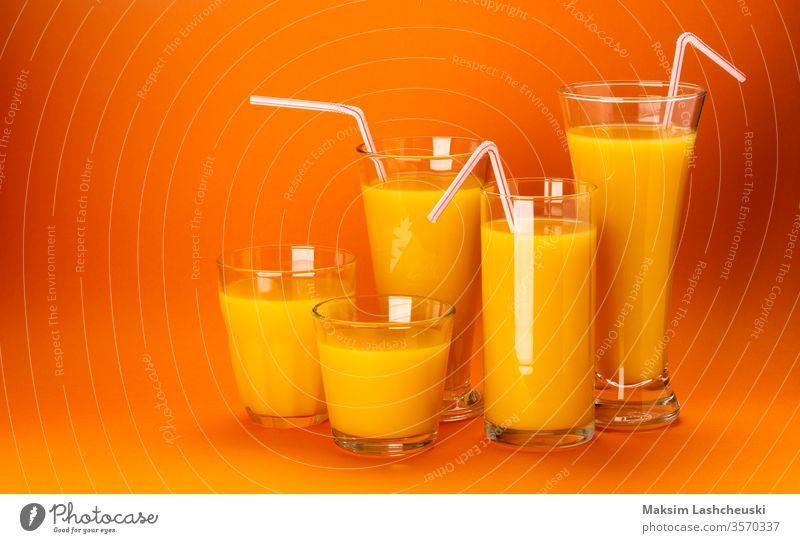 Gläser mit Orangensaft isoliert auf orangefarbenem Hintergrund Glas Saft Textfreiraum frisch Stroh Cocktail Gesundheit Lebensmittel Konzept abschließen