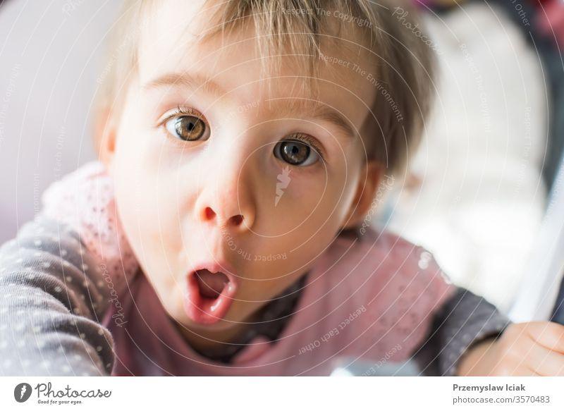 Lustiges Baby in der Krippe im hellen Zimmer. Gesicht Ausdruck Bett Entwicklung Babybett curosity lustig süß bezaubernd Mädchen Kind eine Jahr alt Lebensalter