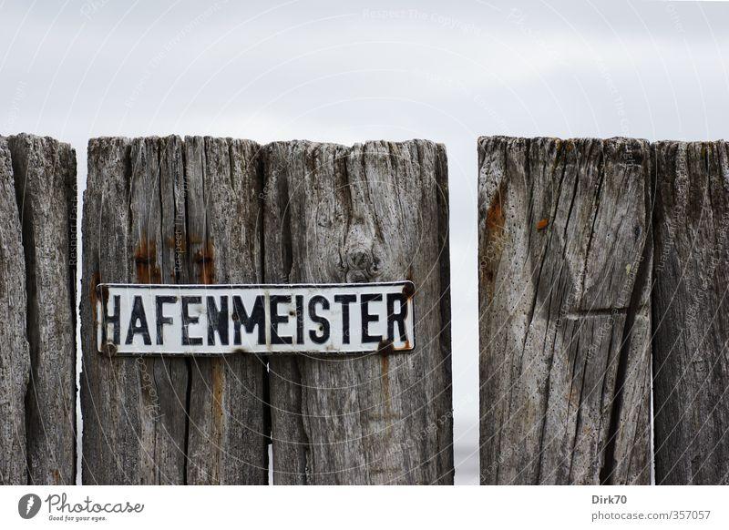 Fällt auch nicht vom Himmel alt weiß Meer schwarz kalt Wand Küste Mauer grau Holz Metall Arbeit & Erwerbstätigkeit Schilder & Markierungen Ordnung Insel Schriftzeichen