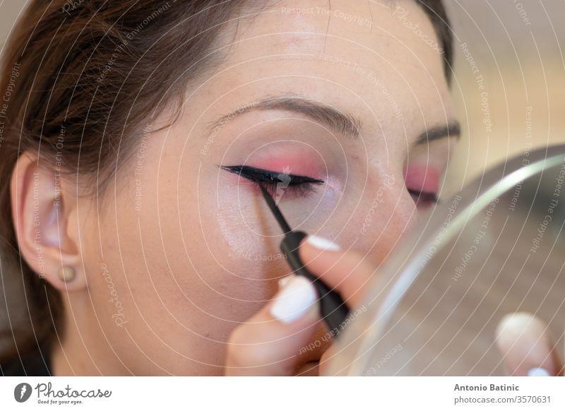Nahaufnahme einer erwachsenen Brünetten beim Auftragen von Eyeliner auf sich selbst, Augen geschlossen, während sie Katzenaugen erzeugt Gesundheit Wimpern