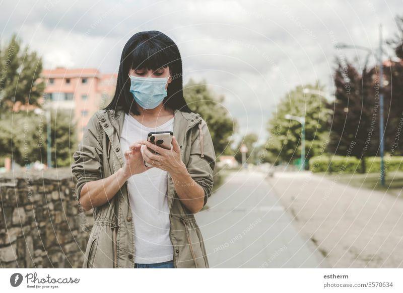 Frau mit medizinischer Maske mit seinem Smartphone auf der Straße Coronavirus Junge Frau Virus Seuche Pandemie Quarantäne covid-19 Telefon App Mobile