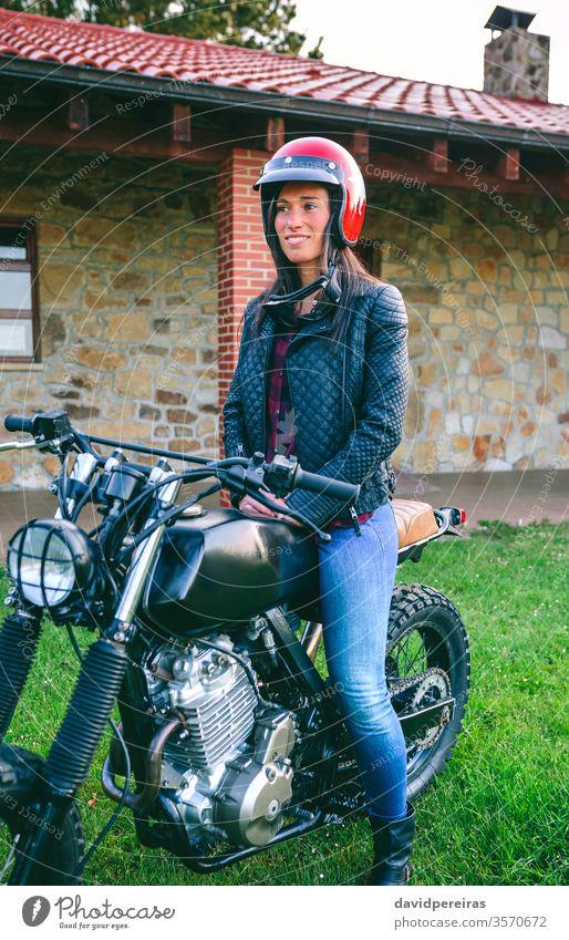 Frau mit Helm auf einem Custom-Motorrad Mädchen Schutzhelm Biker benutzerdefiniert altehrwürdig Fahrrad retro Warten Reiter Fahrzeug schön Model Verkehr
