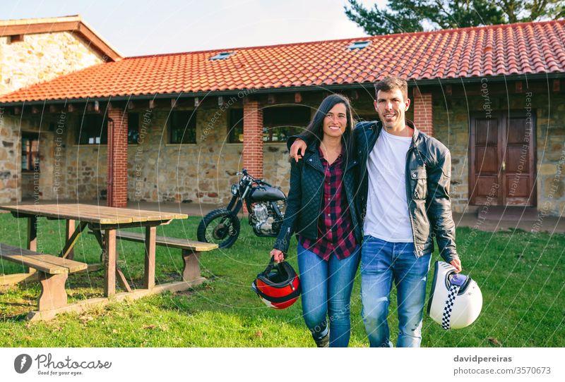 Paar zu Fuß umarmt und benutzerdefiniertes Motorrad attraktiv jung laufen altehrwürdig Haus Picknick-Tisch Fahrrad retro Fahrzeug Biker Verkehr Mode Freundin