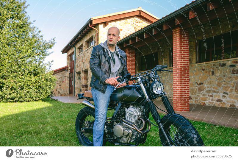 Mann auf einem Custom-Motorrad jung Biker benutzerdefiniert Café-Rennfahrer posierend altehrwürdig Fahrrad retro Reiter Fahrzeug rasierter Kopf Verkehr Mode