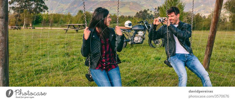 Junger Mann macht ein Foto von seiner Freundin auf der Schaukel Paar fotografierend Fotokamera pendeln Glück Motorrad Lederjacke Biker Transparente Netz