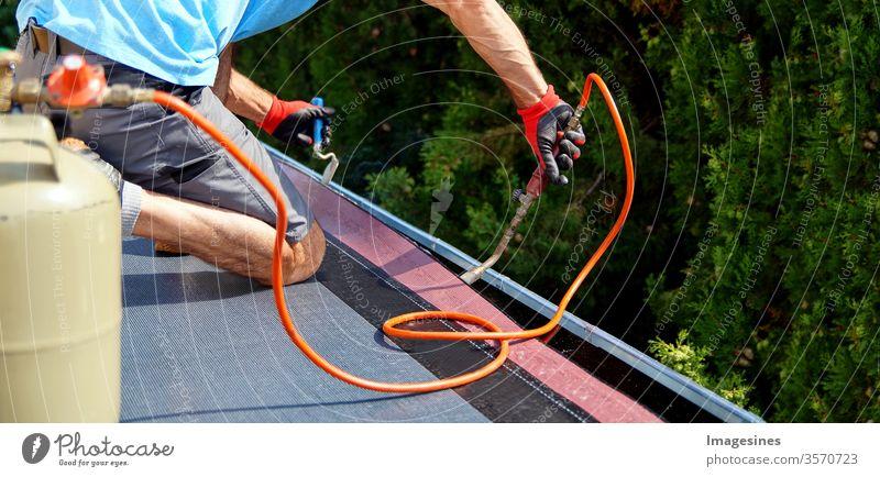 Handwerker - Dachdecker der Teerfolie - Dachpappe - Bitumen auf dem Dach des Gebäudes aufbringt. Flachdach Dachinstallation mit Propan-Lötlampe - Schweissbrenner bei Bauarbeiten mit Dachpappe. Bitumendach