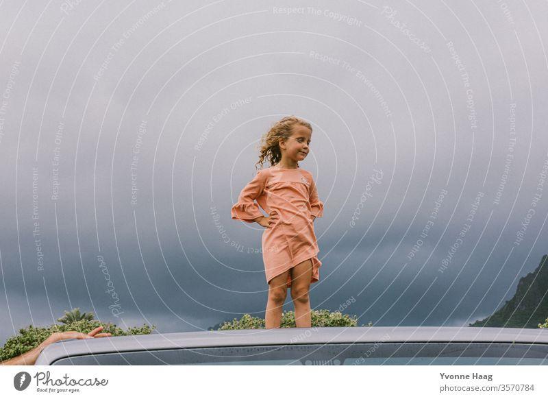 Kind steht auf einem Autodach und der Wind weht ihr das Haar zurück Hawaii Sturm Strand Himmel Küste Wolken Farbfoto Natur Außenaufnahme Landschaft Unwetter