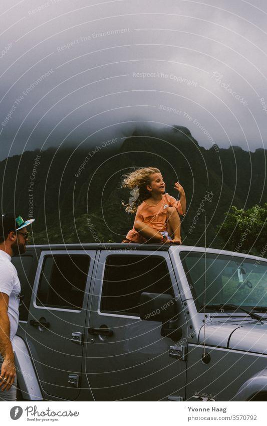 Kind sitzt auf einem Autodach und der Wind weht ihr das Haar zurück Hawaii Sturm Strand Himmel Küste Wolken Farbfoto Natur Außenaufnahme Landschaft Unwetter