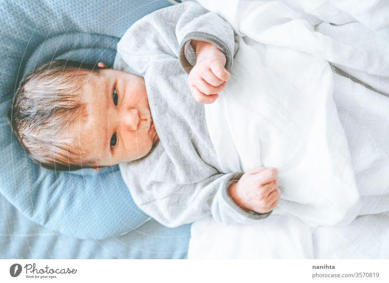 Kleines neugeborenes Mädchen, das sich hinlegt und versucht, sich zu entspannen Baby Neugeborene Geburt erster Tag Junge Mama Familie Glück Fröhlichkeit Pflege