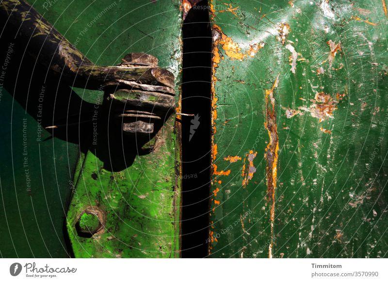 Geheimnisvolle Dunkelheit hinter betagtem Blech dunkelheit Metall grün schwarz Scharnier alt Kratzer Lack Farbe Rost kaputt Nahaufnahme Maschine Neugier