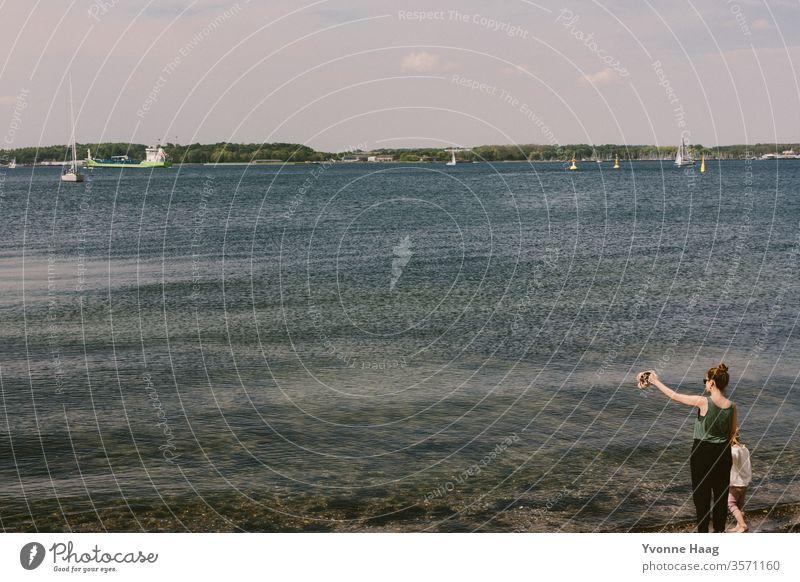 Frau mit Kind am Strand und schaut in die Ferne Sand Meer Wasser Wellen Brandung Küste Himmel blau Wolken Horizont Natur Landschaft weiß Schönes Wetter Sommer