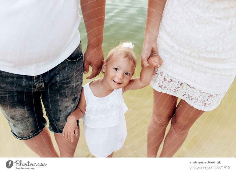 Mama, Papa, Tochter gehen auf Steinen in der Nähe des Sees. Blick nach unten. Ansicht von unten auf die Beine. Das Konzept der Sommerferien. Mutter-, Vater- und Babytag. Die Familie verbringt gemeinsam Zeit in der Natur. Blick der Familie.