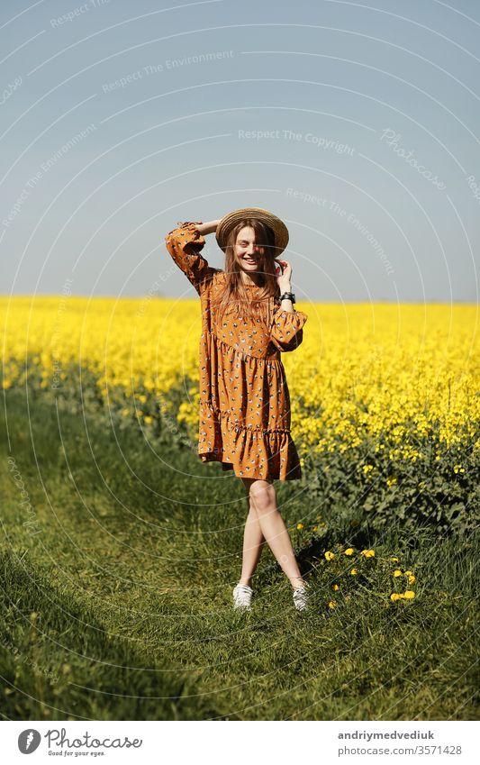 stilvolle junge Frau mit Strohhut in einem Feld mit gelben Blumen. Mädchen im Blütenkleid. Hintergrund mit gelben Blumen und blauem Himmel Porträt Mode Frühling