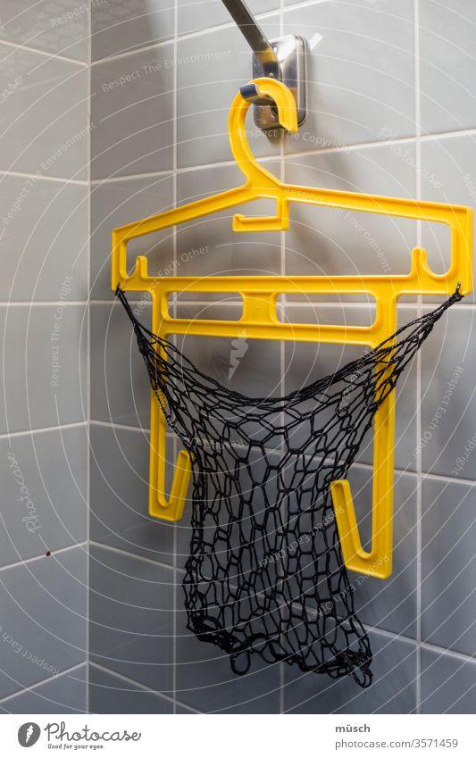 gelber Bügel in Umkleidekabine grau schwarz Plastik Schwimmbad Netz Haken Ecke Kachel Fliesen Sport Kabine Familie Freizeit Garderobe Funktion Spaß Hobby Wasser