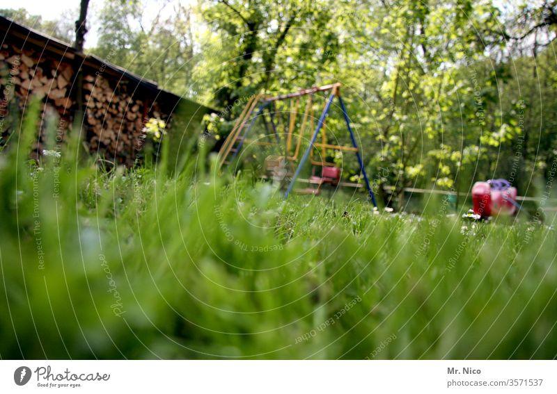 im Garten Wiese Rasen Gras grün Sommer Natur Pflanze Schrebergarten Schaukel schaukeln Spielen Froschperspektive Erholung Idylle Holzstapel Wippe Spielplatz