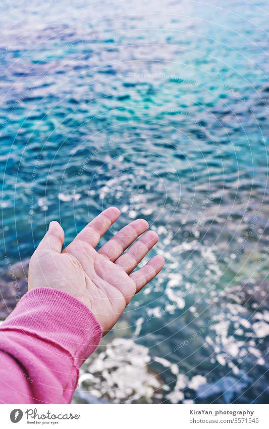 Weibliche Hand mit offener Handfläche greift nach der Wasseroberfläche Tag der Weltmeere Hoffnung Mann Frau Meer MEER Oberfläche blau Konzept pov berühren