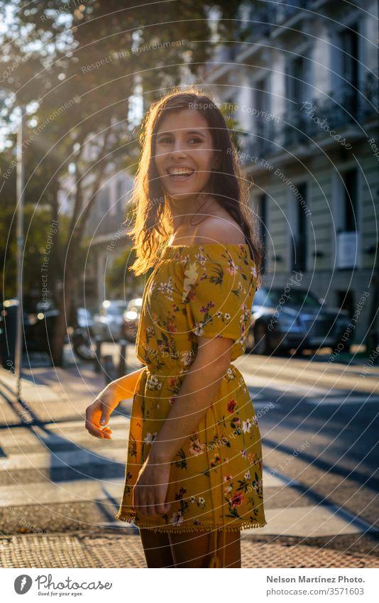 Porträt eines niedlichen Modells zur goldenen Stunde, das ein gelbes Kleid mit Blumendruck trägt. Bokeh Lifestyle Lichter Frau Glamour Stil schön Mensch