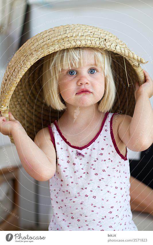 Blondes, gewitztes, kulleräugiges Mädchen im geblümten Unterhemd, stülpt sich einen großen, beigen Korb, in Naturmaterialien über den Kopf und schaut in die Kamera. Lustiges, witziges, ideenreiches, kreatives Kinderspiel zuhause, in der hellen Wohnung.
