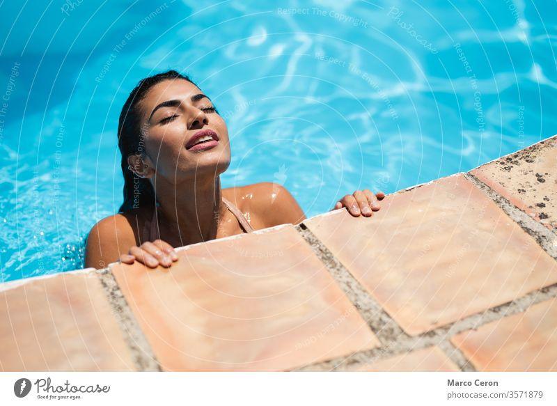 Junge Frau mit gemischtem Rennen entspannt sich im Wasser im Schwimmbad gemischte Rasse schön jung attraktiv Pool Bikini Bräune Haut Mädchen Sonnenbad Urlaub