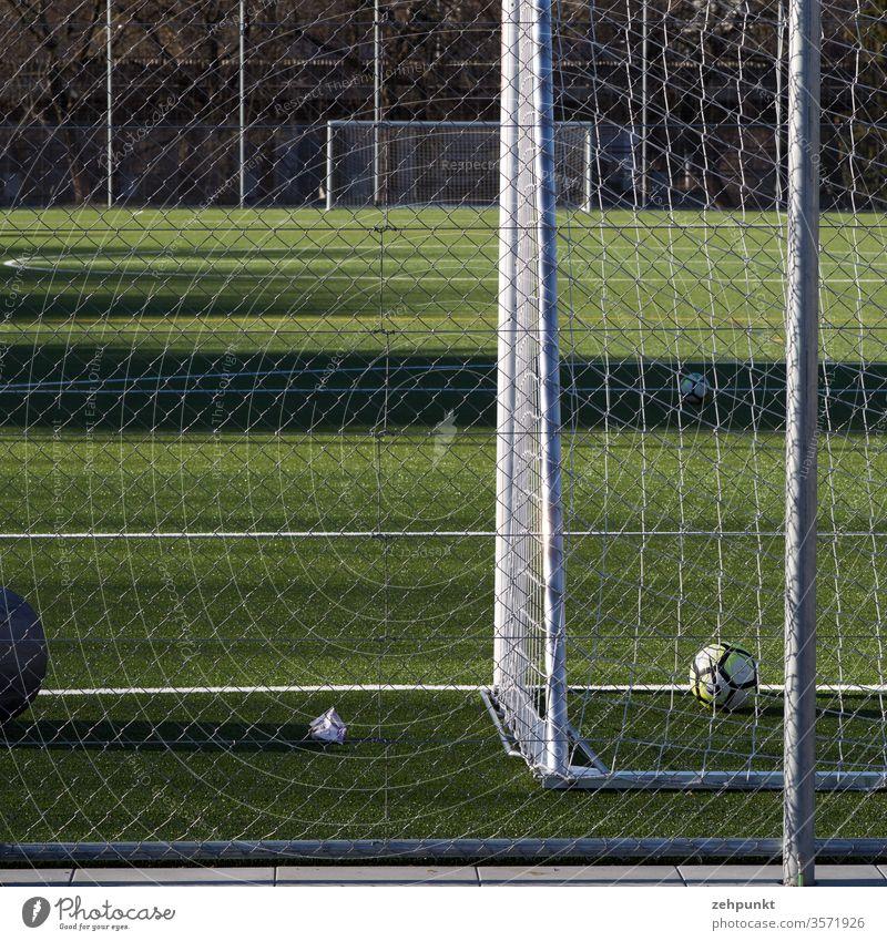 Blick längs des Fussballfeldes von Tor zu Tor. Das vordere Tor ist angeschnitten, ein Ball liegt hinter der Linie, weite seitliche Schattenwürfe auf das Spielfeld