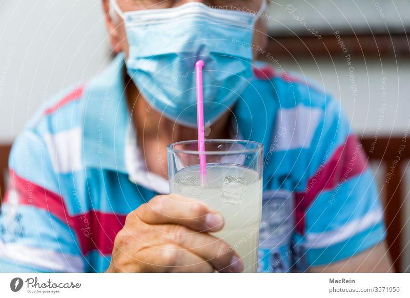 Mann trinkt mit einem Strohhalm durch den Mundschutz mundschutz corona COVID-19 sylt mallorca norderney föhr baltrum wangerooge büsum helgoland urlaub ferien