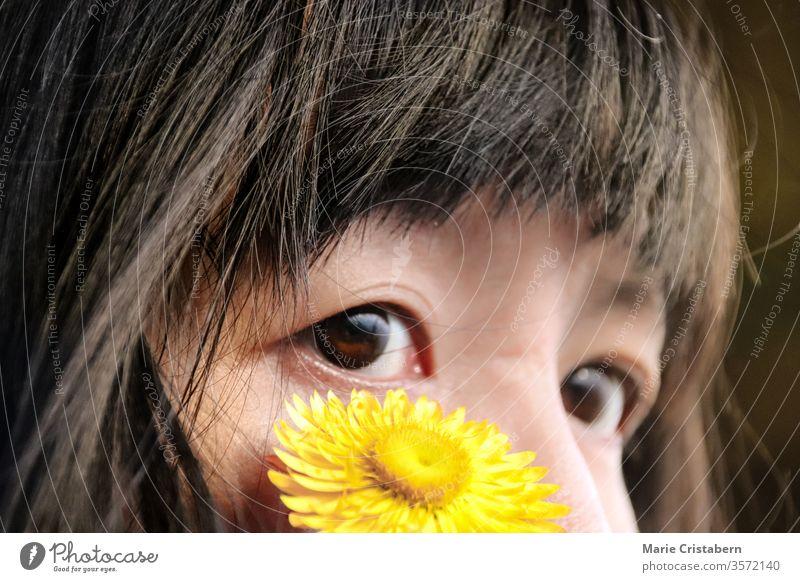 Nahaufnahme einer gelben Blume auf dem Gesicht eines asiatischen Mädchens mit Mandelaugen Unschuld Reinheit Kindheit Porträt Glück Farbfoto Ausdruck Gefühle
