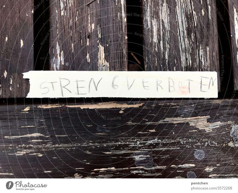 Die Wörter streng verboten stehen in kinderschrift  auf einem Streifen aus  Papier, der auf einem  alten Holztisch liegt,  bei dem der Lack absplittert  Erziehung, Pädagogik, strenge