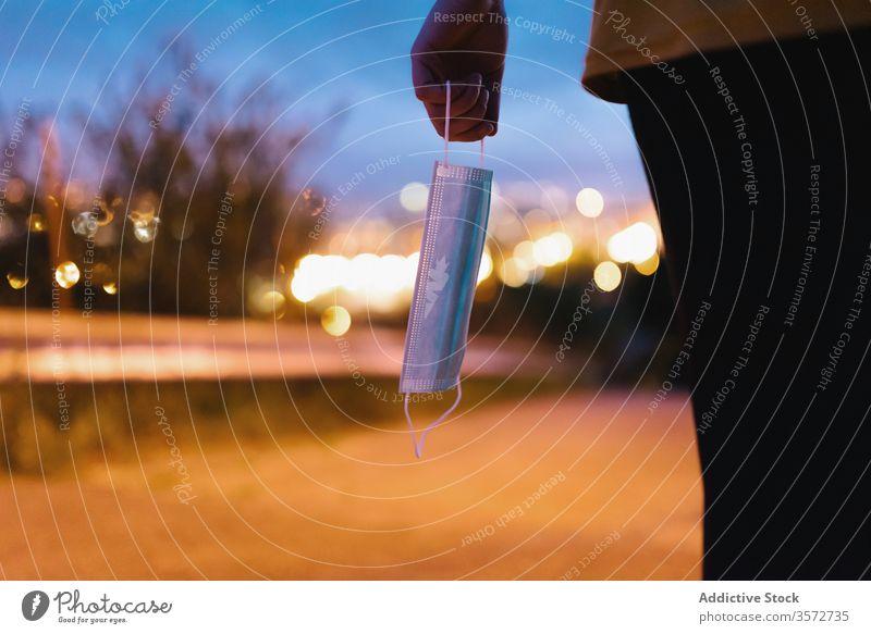 Unerkennbare Person, die abends auf der Straße eine medizinische Maske in der Hand hält Mundschutz Pandemie dunkel urban Infektion COVID19 Pflege Bund 19