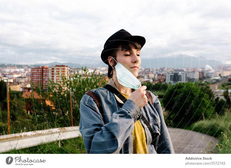 Seriöse junge Frau mit medizinischer Maske steht auf der Straße in der Stadt Mundschutz Atem urban COVID19 frisch Air ernst Coronavirus Ausbruch Sperrung