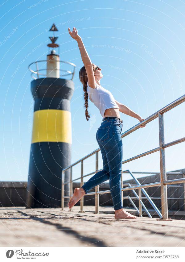 Zufriedene Frau mit erhobenem Arm am Wasser Hafengebiet Inhalt verträumt Stauanlage Leuchtturm genießen Strandpromenade sich[Akk] entspannen Sommer reisen