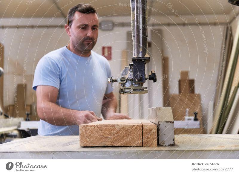 Aufmerksamer Erwachsener sägt Holz im Arbeitsraum Mann Säge Maschine Nutzholz Schreinerei geschnitten Zimmerer Schiffsplanken Werkstatt Tischler Gerät