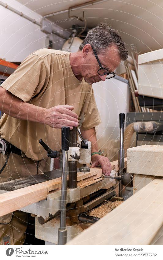 Fleißiger Zimmermann bohrt Holz in modernem Arbeitsraum Zimmerer bohren Schreinerei Nutzholz Holzarbeiten Verarbeitung Kunsthandwerk Mann Werkstatt Arbeitsplatz