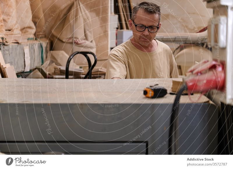 Seriöser Holzarbeiter bei der Arbeit in einer zeitgenössischen Werkstatt Handwerker Maschine verwenden Schreinerei Mann Meister Holzarbeiten Arbeiter Tischler