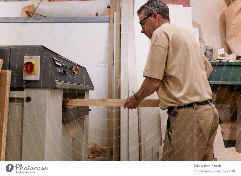 Sorgfältig nachdenklicher Holzarbeiter beim Hobeln von Holzbalken mit der Maschine in einer zeitgenössischen Werkstatt Meister Holzarbeiten Grinden Zimmerer