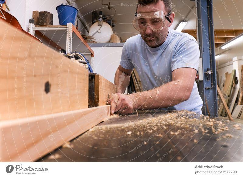 Holzfacharbeiter mit Fräse bei der Arbeit mit Holz in einem modernen Arbeitsraum Zimmerer Fräsen Maschine Brille Werkstatt Sägemehl Sicherheit Mann