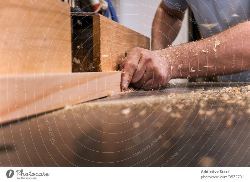 Handwerker fräst Schnittholz mit der Maschine in der Schreinerei Fräsen Sägemehl Nutzholz Mann Kunsthandwerker Holzarbeiten Tischler Arbeitsraum präzise Meister