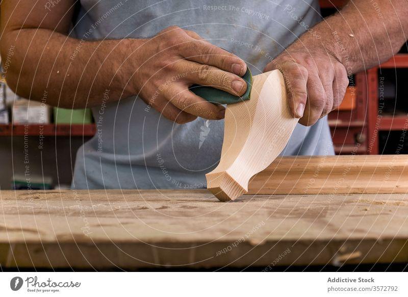 Handwerkliches Polieren von Holzdetails mit Sandpapier in der Schreinerei Kunstgewerbler polnisch Schleifpapier Detailaufnahme Kontrolle Holzarbeiten Meister
